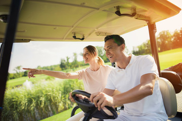 Couple riding a white golf cart on the golf course