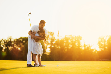 A man is teaching his daughter to play golf. He guides her, the girl is getting ready to make her first punch in golf
