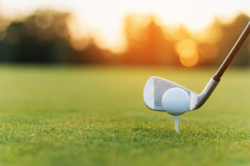 The golf club behind the golf ball on the stand. Against the background of grass and sunset