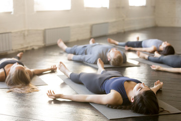 Group of young sporty people practicing yoga lesson in gym, lying in Corpse exercise doing Savasana pose, friends relaxing after working out in sport club, indoor image. Wellbeing and wellness concept