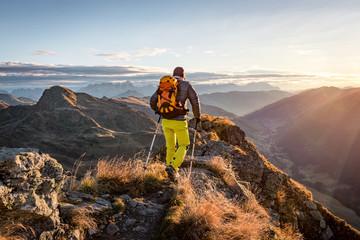 Alpinista wycieczkuje w górach w ranku świetle