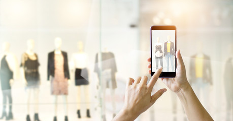 Hands using mobile smart phone and take a photo on display of a clothing store, online shopping concept