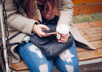 girl sitting in Park with phone and coffee