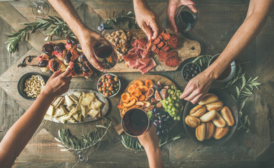 Flat-lay of friends eating and drinking together. Top view of people having party, gathering, celebrating at wooden rustic table set with various wine snacks and fingerfoods. Hands holding glasses