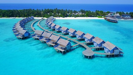 P01226 Aerial flying drone view of Maldives white sandy beach on sunny tropical paradise island with aqua blue sky sea water ocean 4k luxury 5 star resort hotel water bungalow hut relaxing holiday