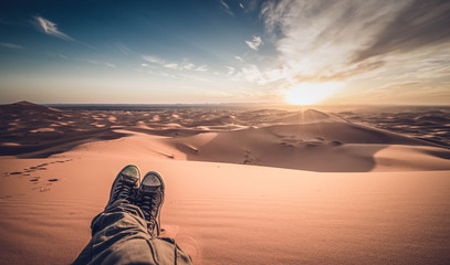 A man is enjoying the sunset on the dunes in the Sahara Desert - Merzouga - Morocco