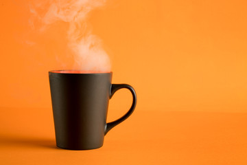 Coffee cup with steam on orange