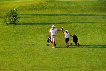 man with his son golfers walking on perfect golf course at summer evening