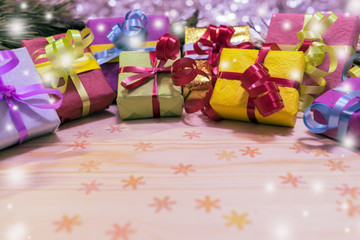 New-year colored boxes with gifts at a Christmas tree with cones on a wooden background