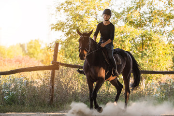 Young pretty girl riding a horse with backlit leaves behind