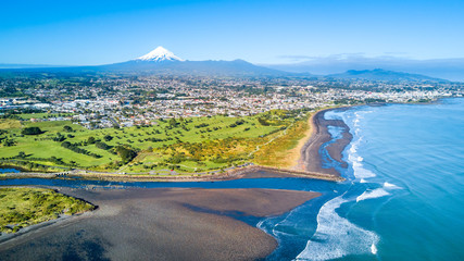 Aerial view on Taranaki coastline with a small river and New Plymouth and Mount Taranaki on the background. Taranaki region, New Zealand