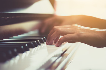 Close up of happy woman's hand playing the piano in the morning.