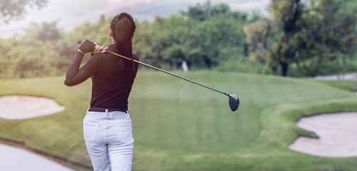 Young women player golf swing shot on course