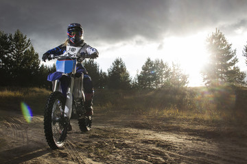 A portrait of motocross rider sitiing on the bike on the background of sunset