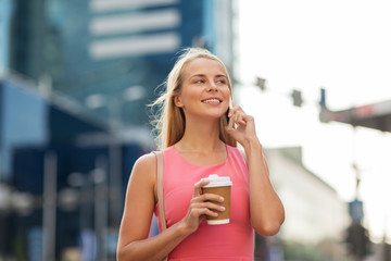 woman with coffee calling on smartphone in city