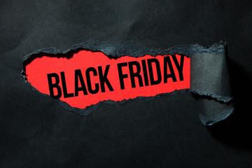 """Czarny podarty papier i napis """"czarny piątek"""" na czerwonym tle."""