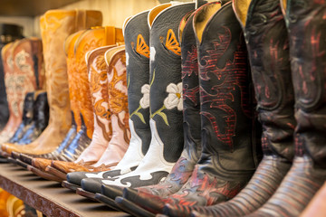 Cowboy boots on a shelf in a store aligned