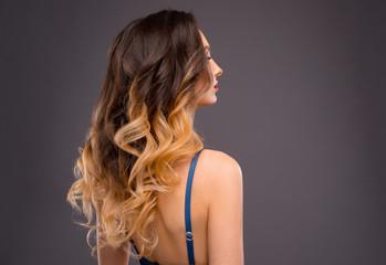 Kobieta z długie zdrowe kolorowe włosy faliste Ombre. Fryzura z bliska