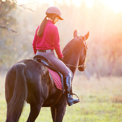 Rear view of teenage girl riding horse in park at sunset. Young rider girl on bay horse in the autumn park