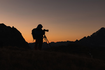 Photographer in the Dolomites taking pictures of sunset. Silhouette of a photographer on a golden background. Dolomites.