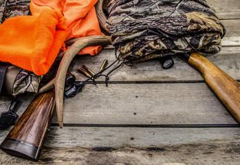 Tło polowania na jelenie. Karabiny myśliwskie, luneta, poroże, pociski i odzież myśliwska na rustykalnym drewnianym tle z miejsca kopiowania.