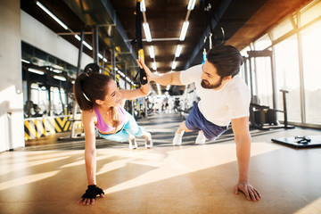 Young beautiful fitness couple smiling and clapping hands each other while doing push ups together in the gym.