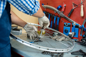 Male hands in textile gloves fixing bolt on central part of bicycle wheel