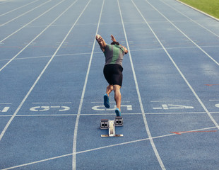 Sprinter taking off from starting block on track