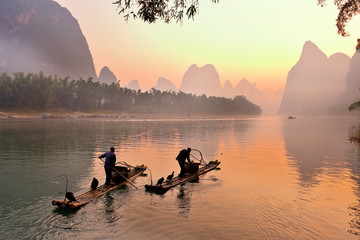 Silhouette of Two Fishing Men and His Cormorants on Li River at Sunrise, Guilin, China. The Li River or Lijiang is a river in Guangxi Zhuang Autonomous Region, China.