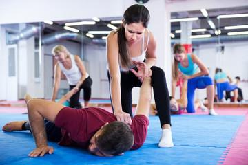 Dziewczyna wykonuje ruchy samoobrony z trenerem
