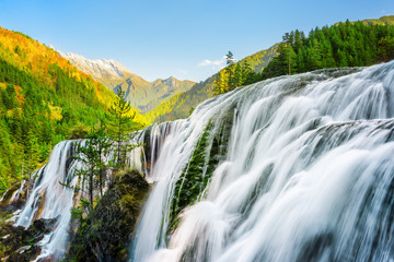 Amazing view of the Pearl Shoals Waterfall among woods at sunset