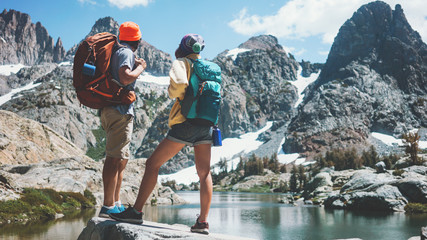 Young active backpackers couple rock climbing together in stunning mountain wilderness near the snowy lake. Looking at breathtaking natural landscape