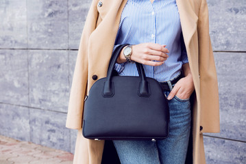Trendy woman in beige coat and jeans with black big bag