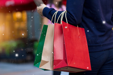 Christmas shopping - shopping bags in hand with snowflake on christmas decoration and lighting on street background