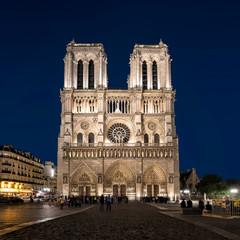 Paris, France - October 17, 2017: Night view of West facade at cathedral Notre Dame de Paris. Unidentified people present on picture. Copy space in sky.