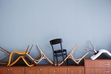 Chairs piled on chest of drawers against light wall