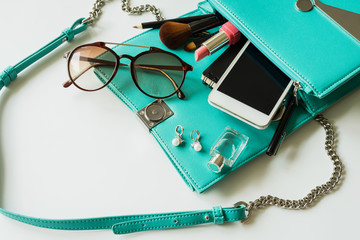 Woman handbag with makeup, cellphone and accessories