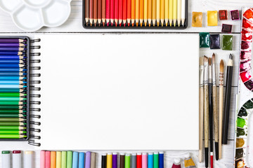 Artist workspace on white wooden background.