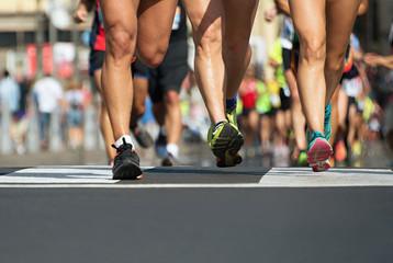 Marathon running in the light of evening,runners running on city road,detail on legs