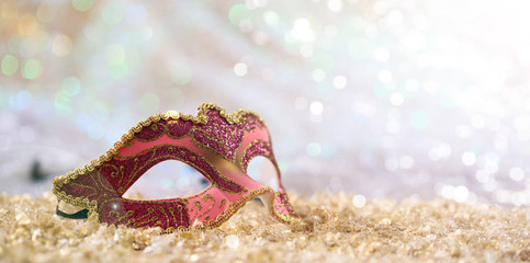 Pink carnival mask on bokeh background
