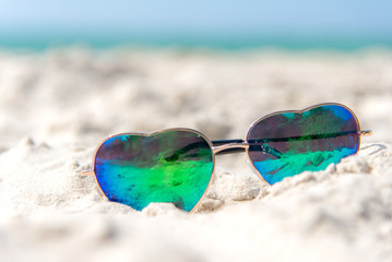 Summer Fashion heat shape sunglasses on sea beach under clear blue sky. Summer holiday relax background with copy space.