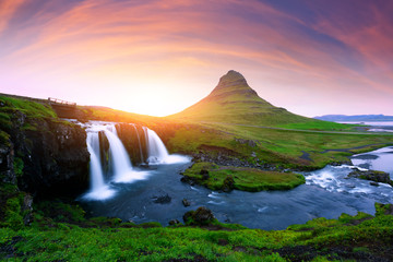 Picturesque icelandic landscape with colorful sunrise on Kirkjufellsfoss waterfall. Amazing morning scene near famous mountain - Kirkjufell volkano, Iceland, Europe
