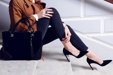 Zbliżenie nóg kobieta w czarnych szpilek butach siedzi na białych schodkach.