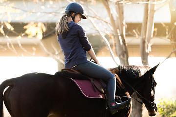 Młoda ładna dziewczyna - jazda na koniu z podświetlanymi liśćmi