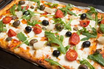 Pizza vegetariana con mozzarella, sugo, pomodorini, rucola, cipolle, olive, capperi e origano
