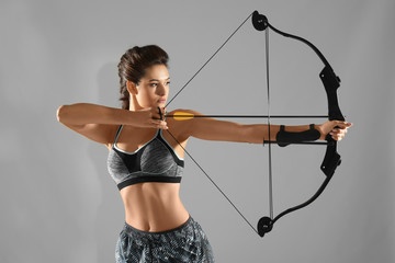 Sporty young woman practicing archery on grey background