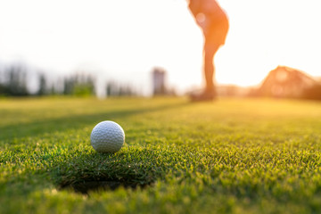 Golfista kobiety kładzenia azjatykcia piłka golfowa na zielonym golfie na słońce wieczór ustalonym czasie, wybrana ostrość. Koncepcja zdrowego stylu życia.