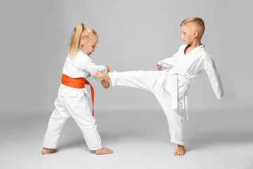 Little children practicing karate on light background