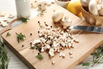 Fresh sliced champignon mushrooms on wooden board