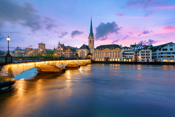 Panoramic view of historic Zurich city center with famous Fraumunster Church and river Limmat at Lake Zurich , in twilight, Canton of Zurich, Switzerland.